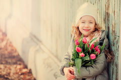 Spring vintage tones portrait of happy child girl with tulips bouquet for woman's day Royalty Free Stock Photo