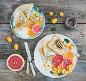 Spring vitamin breakfast set. Thin crepes or pancakes with fresh grapefruit, orange, kumquat, honey, cream and mint leaves over a Stock Photography