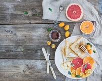 Spring vitamin breakfast set. Thin crepes or pancakes with fresh grapefruit, orange, kumquat, honey, cream and mint leaves over a Stock Image