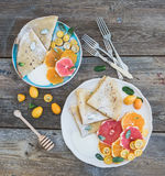 Spring vitamin breakfast set. Thin crepes or pancakes with fresh grapefruit, orange, kumquat, honey, cream and mint leaves over a Royalty Free Stock Photography