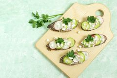 Spring vitamin toasts with cottage cheese, radish and cucumber. Spring vitamin toast from whole wheat bread with sesame and poppy seeds. Toasts are spread Stock Photography