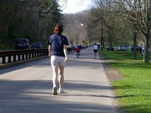Spring walk 1. Single woman walking in the park Royalty Free Stock Images