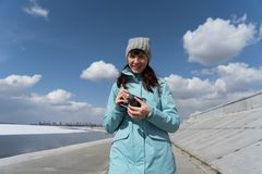 Spring walk: a girl in a blue jacket walks along the embankment and takes pictures on an old film camera. Portrait stock photo