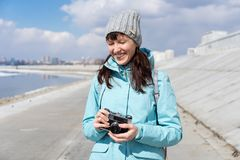 Spring walk: a girl in a blue jacket walks along the embankment and takes pictures on an old film camera. Portrait royalty free stock photography
