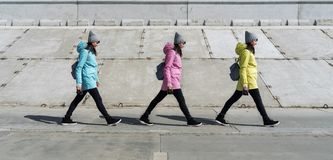 Spring walk: a girl in different color jackets walks on a concrete surface on a gray background. Wide step stock photo