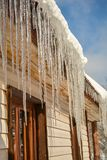 Icicles on a sunny day hang from a heated roof royalty free stock images