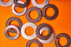 Spring washers on orange background. Bolted connection elements.  royalty free stock photography