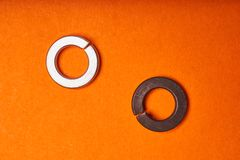 Spring washers on orange background. Bolted connection elements.  royalty free stock image