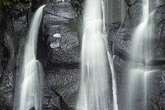 Spring water falls. White thread like lines spring water which falls along a rock wall Stock Photo