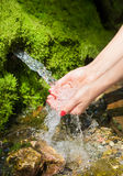 Spring water flows in female hands Stock Photo