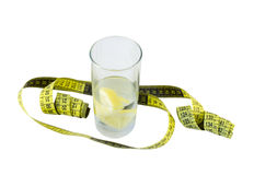 Water with lemon in glass and yellow centimeter Royalty Free Stock Photography