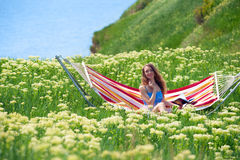 Spring week-end. Smiling pretty woman sitting in a hammock among the blooming yarrow Royalty Free Stock Photo