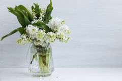 Spring white lilac and lily of the valley bouquet in a vase on w Royalty Free Stock Photos