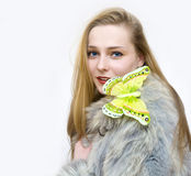 A spring will come soon. A girl in a fur coat by a cold winter holds a butterfly stock photo