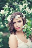 Spring woman portrait. Perfect young model on spring flowers and green leaves background outdoor royalty free stock photo