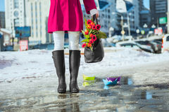 Spring. Woman wearing rain boots stay into a puddle Royalty Free Stock Photos
