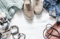 Spring women`s clothing in pastel colors - jeans, pullover, suede shoes, leather bag and bracelets on a light background. Spring womens clothing in pastel colors stock photography