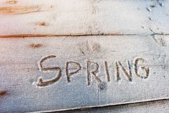 Spring written on a wooden background with frosts Royalty Free Stock Photos