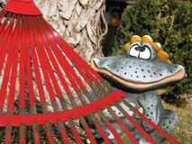 Spring yard clean up can be fun. Red rake against a tree trunk with a funny smiling frog statue looking on stock photos