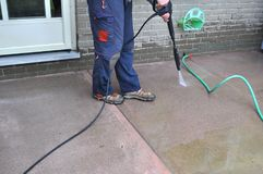 Man cleaning a sidewalk with a pressure washer during spring yard and garden work. Spring yard work - man cleaning a sidewalk with a pressure washer. Man Royalty Free Stock Photos