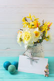 Spring yellow daffodils flowers in vase,  Easter eggs  and empty Stock Image