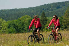 Spring - Young couple riding in nature. Young man and woman riding mountain bikes in summer nature Royalty Free Stock Images