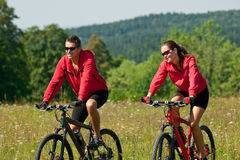 Spring - Young couple riding in nature. Young man and woman riding mountain bikes in summer nature Stock Images
