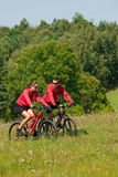 Spring - Young couple riding in nature. Young couple riding mountain bikes in summer nature Stock Images