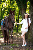 Spring young pretty girl near horse. Spring, forest, sunny day, beautiful woman with wreath of flowers, shiny smile, white suit, standing near big brown horse Royalty Free Stock Image