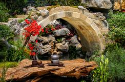 Spring zen garden with curvy stone bridge. Spring zen garden with stone curvy bridge during summer stock images