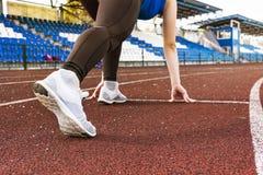 Springa den färdiga och säkra kvinnan i den startande positionen som är klar för att köra Kvinnlig idrottsman nen omkring som ska Royaltyfri Bild