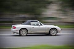 Springa för Cabrioletbil på vägen Cabriolet med en stängd överkant som rusar ner vägen Allt är suddigt Royaltyfri Foto