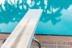 Springboard to dive at swimmingpool Stock Photos