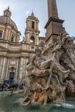 Springbrunn av de fyra floderna i bakgrunden den kyrkliga Santen Agnese i piazza Navona i Rome Royaltyfri Foto