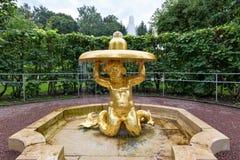 Springbrunn`en Triton - sätta en klocka på ` i trädgården av lägre parkerar Peterhof St Petersburg, Royaltyfria Bilder