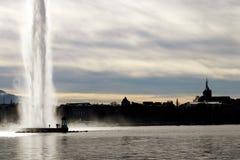 Springbrunn för dEau för stråle för Genèvecityscapevatten och Saint Pierredomkyrkakontur i vinter royaltyfri fotografi