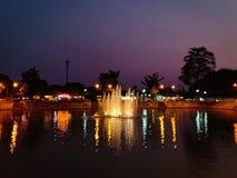Springbrunn i dammet på natten royaltyfri bild