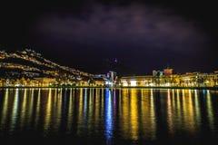Springbrunn i nattljuset och en trevlig vattenreflexion Arkivfoto