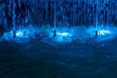 Springbrunn med blåa belysningar på natten Arkivbilder