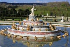 Springbrunn med förgyllda prydnader till parkera av Versailles Arkivbild