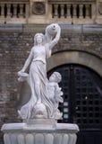 Springbrunn med marmorstatyer nära en slott Fotografering för Bildbyråer