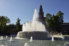 Springbrunn och Castello Sforzesco i Milan Arkivbilder