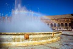 Springbrunn och regnbåge på fyrkant av Spanien i Seville, Spanien royaltyfri bild