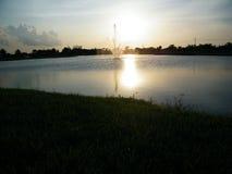 Springbrunn och solnedgång Arkivfoto