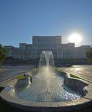 Springbrunn på den Unirii boulevarden med parlamentet och aftonsolen som Royaltyfri Fotografi