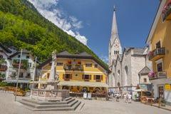 Springbrunn på Marktplatz, fyrkant för historisk stad av Hallstatt med kyrkliga och traditionella färgrika hus, Österrike royaltyfri bild
