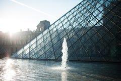 Springbrunnen grundar på den Glass pyramiden Paris Frankrike royaltyfri bild