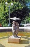Springbrunnen i den Strukovsky trädgården med den etablerade bronsskulpturen av pojken och flickan under ett paraply i den soliga Fotografering för Bildbyråer