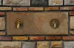 Springbrunnen med de två gamla bronsklappen med hjärtan drunknar in - between Royaltyfria Foton