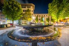 Springbrunnen och byggnader på packen kvadrerar på natten, i i stadens centrum Ashe Arkivbild